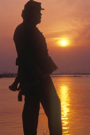 ga: Silhouette of soldier at sunset during Civil War reenactment, Savannah, GA