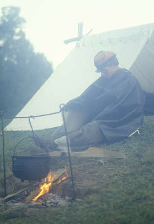 Civil War confederate soldier participant by fire with tent in camp, Vicksburgh, MI