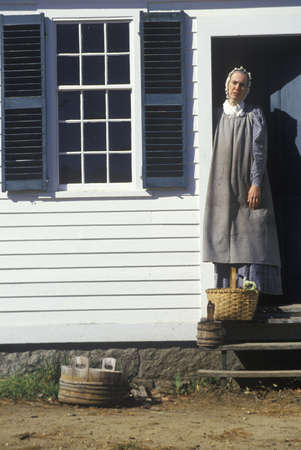 Woman in period clothing in doorway to house in Old Sturbridge, Historic town in MA