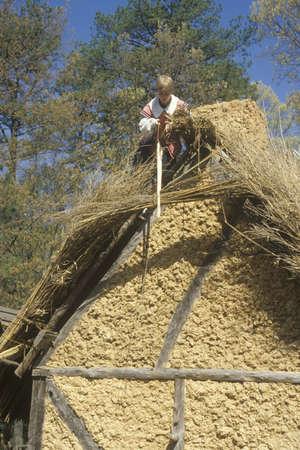 reenactor: Participante trabaja en la azotea con techo de paja en la hist�rica Jamestown, Virginia, sede de la primera colonia de Ingl�s