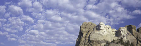 busts: Panoramic image with white puffy clouds behind Presidents George Washington, Thomas Jefferson, Teddy Roosevelt and Abraham Lincoln at Mount Rushmore National Memorial, South Dakota