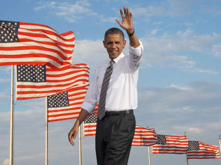 President Barack Obama waving against a backdrop of flags of the United States of America Editorial