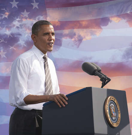 President Barack Obama speaking against a backdrop of the flag of the United States of America Editorial