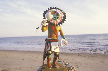 wingspread: Hopi Kachina doll holding objects on beach with ocean in the background