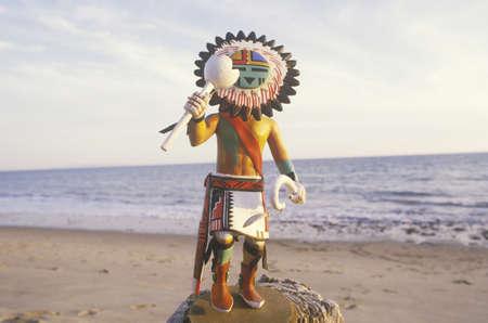 hopi: Hopi Kachina Doll porta oggetti sulla spiaggia con il mare sullo sfondo Editoriali