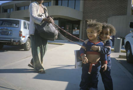tether: Two African-American children on their mothers leash, Los Angeles, CA Editorial