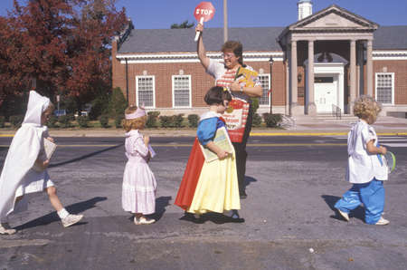 helping children: School crossing guard helping children in Halloween costumes, Webster Groves, Missouri