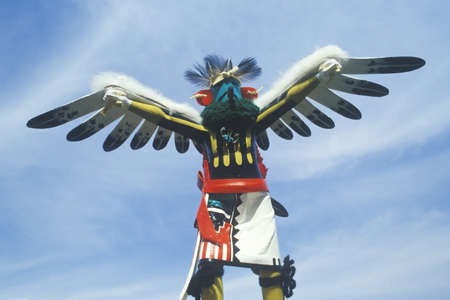 hopi: Hopi Kachina doll with outstretched winged arms against blue sky