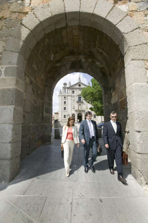 spaniards: Three business people walk through gate of walled city, Avila Spain, an old Castilian Spanish village Editorial