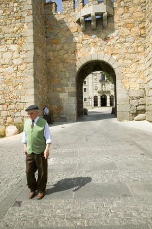 spaniards: Well-dressed older man with hat walks through gate of walled city, Avila Spain, an old Castilian Spanish village Editorial