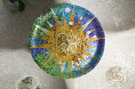 Colored wheel mosaic of colored ceramic tile by Antoni Gaudi at his Parc Guell, Barcelona, Spain