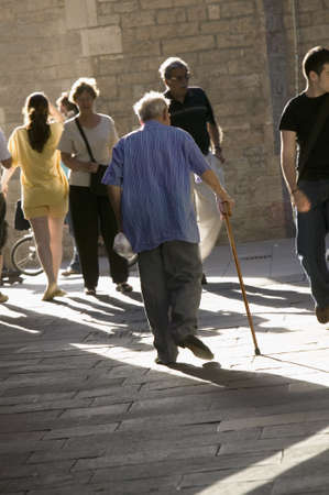 Old man with cane walks down crowded old section of Barcelona, Spain, in Barri Gotic area which is also known as the Gothic Quarter