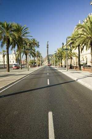 クリストファー ・ コロンブスの像を見下ろす Passeig de Colom のポート ・ ベル、バルセロナ、スペインのウォーター フロントの横にある道路 報道画像