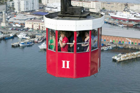 Red tram of tourists look at view of Estacio Maritima, Port Vell the (Old Harbour) of Barcelona, Spain