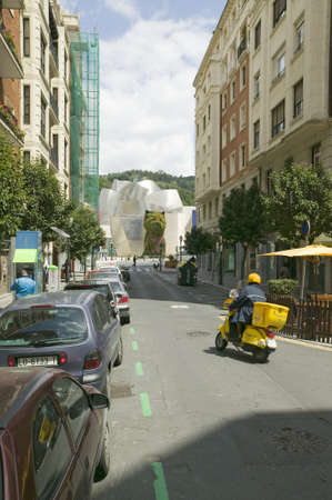 Yellow motorcycle drives toward The Guggenheim Museum of Contemporary Art of Bilbao (Bilbo), located on the North Coast of Spain in the Basque region. Nicknamed The Hole, this is a contemporary museum built of titanium, limestone and glass and was desig