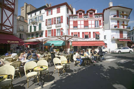awnings: St. Jean de Luz, on the Cote Basque, South West France, a typical fishing village in the French-Basque region near the Spanish border, shows the cute village with red awnings and shutters