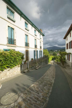 Path between homes in Sare, France in Basque Country on Spanish-French border, a hilltop 17th century village in the Labourd province. The houses are built in the traditional style of the region, with shutters painted colors red and green of the Basque fl