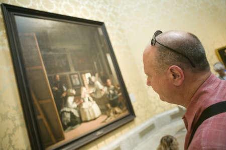 velazquez: Man looks at Las Meninas by Velazquez as shown in the Museum de Prado, Prado Museum, Madrid, Spain