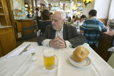 spaniards: 100 year old man sits down to a mug of beer and  a loaf of bread in a restaurant in Madrid, Spain