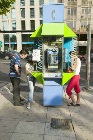 spaniards: Bright green telephone booth being used on the summer sidewalks of Madrid, Spain Editorial