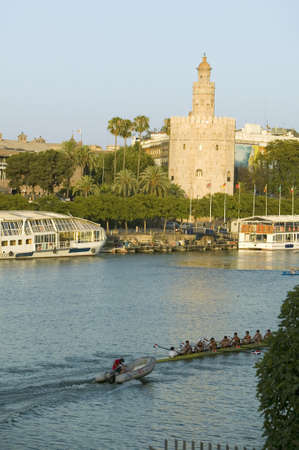Rowers row by octagonal tower of Torre del Oro makes golden reflection on Canal de Alfonso of Rio Guadalquivir River, Sevilla Spain