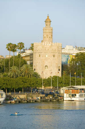 View of the octagonal tower of Torre del Oro makes golden reflection on Canal de Alfonso of Rio Guadalquivir River, Sevilla Spain