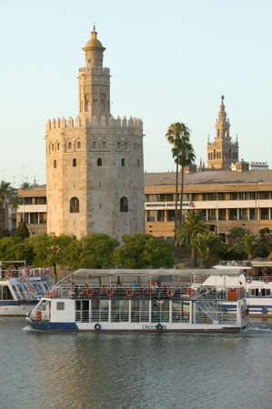 View of the tour boats and octagonal tower of Torre del Oro makes golden reflection on Canal de Alfonso of Rio Guadalquivir River, Sevilla Spain