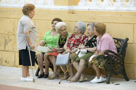 Older women with canes talk on bench in village of Southern Spain off highway A49 west of Sevilla 新聞圖片