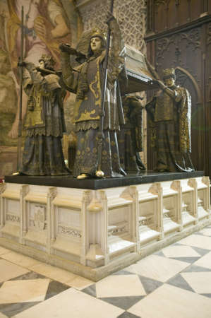 lon: In the Sevilla Cathedral, Southern Spain, is the mausoleum-monument and ornate tomb of Christopher Columbus where four heralds dressed in full court mourning carry the sarcophagus; they bear respectively the arms of, Castile, L�on, Aragon, and Navarre, th Editorial