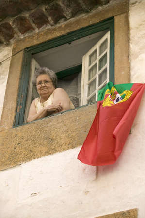 An older woman celebrates soccer victory by hanging Portuguese flag out the window of Tomar, Portugal