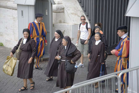 Nuns and brightly colored uniforms of Swiss Guard at Vatican City, center of Catholic Church, Rome, Italy, Europe Editorial