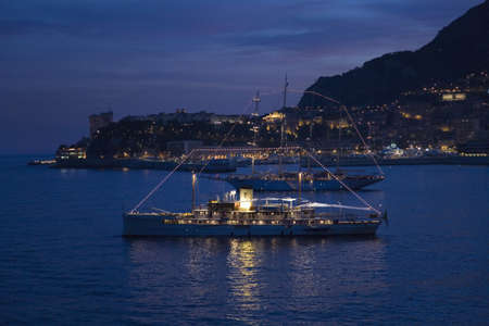 Yacht and seaside night view of Monte-Carlo with lights at dusk, in the Principality of Monaco, Western Europe on the Mediterranean Sea