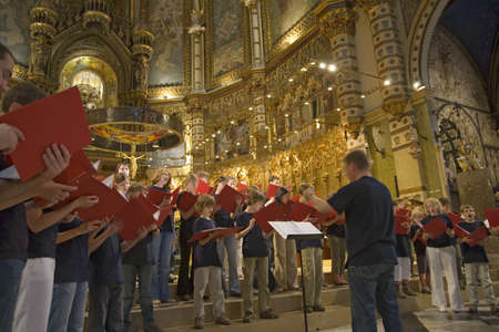 Boys & girls choir singing in the Benedictine Abbey at Montserrat, Santa Maria de Montserrat, near Barcelona, Catalonia, Spain with Black Madonna in background