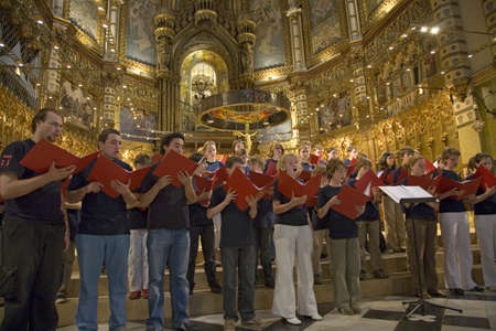 Boys & girls choir sing in the Benedictine Abbey at Montserrat, Santa Maria de Montserrat, near Barcelona, Catalonia, Spain with Black Madonna in background