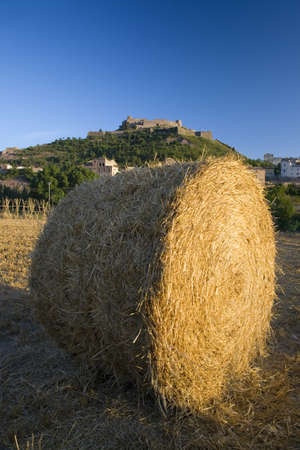 pile dwelling: Hay bails in foreground with background of Parador de Cardona, a 9th Century medieval hillside Castle, near Barcelona, Catalonia, Cardona, Spain Editorial