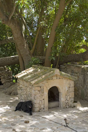Dog house with sleeping dog at Camino d els Calderers d San Juan, Majorca, the largest island of Spain, Europe on the Mediterranean Sea and part of Balearic Islands archipelago