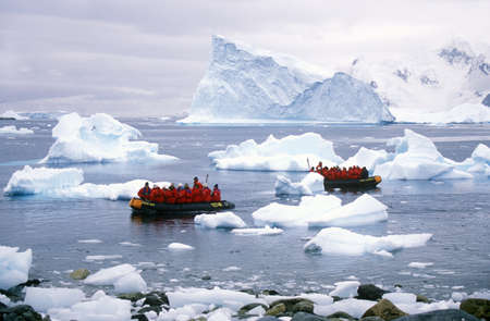 sightseers: Ecological tourists in inflatable Zodiac boat in Paradise Harbor, Antarctica