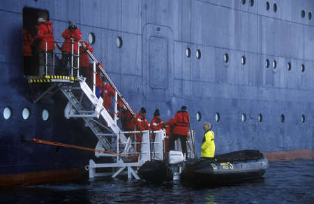 sightseers: Ecological tourists enter inflatable Zodiac boat from cruise ship Marco Polo in Errera Channel at Culberville Island, Antarctica Editorial