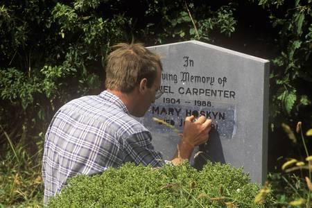 A man carving a gravestone at Kilcatherine Church in Cork, Ireland