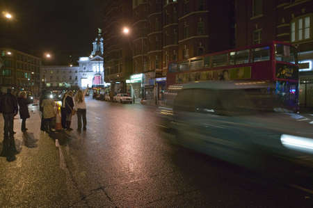 Hailing a cab on wet night streets of West End of London's theater district with double decker bus driving by, England