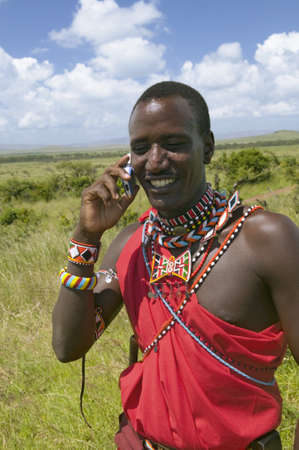 Masai in red toga talks on his cell phone from the grasslands of the Lewa Wildlife Conservancy in North Kenya, Africa