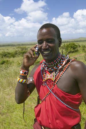 conversa: Masai en rojo toga habla en su tel�fono celular de los pastizales del Lewa Wildlife Conservancy en el norte de Kenia, �frica