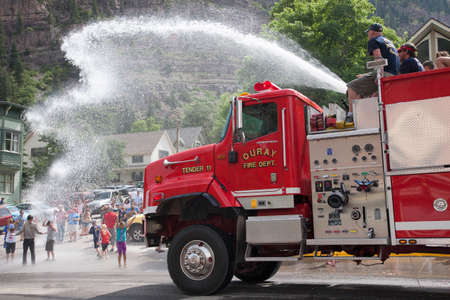 Ouray Firetruck squirts off kids in July 4 Independence Day Parade, Ouray, Colorado