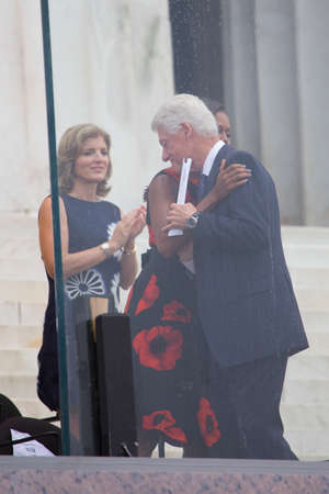 Former US president Bill Clinton hugs First Lady Michelle Obama as Caroline Kennedy claps during the Let Freedom Ring Commemoration marking the 50th anniversary of the March on Washington at the Lincoln Memorial in Washington, DC on August 28, 2013.