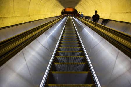 Een roltrap met passagiers door ovale buis van licht verplaatst zich naar het Washington DC Metrorail forensentreinen Redactioneel