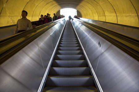 Een roltrap met passagiers door ovale buis van licht om het Washington DC Metrorail forensentreinen beweegt Redactioneel