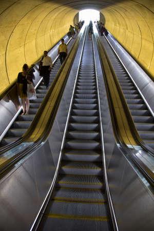Een roltrap met passagiers door ovale buis van licht om de Washington DC Metrorail forensentreinen beweegt
