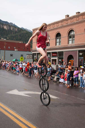 Unicyclist bicycles  in July 4 Independence Day Parade, Ouray, Colorado