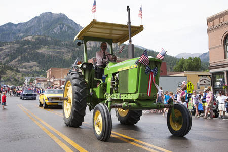 Green tractor drives in July 4 Independence Day Parade, Ouray, Colorado