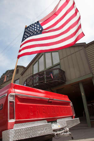 US Flag flies over old red chevrolet pickup truck, July 4 Independence Day Parade, Ouray, Colorado Stock Photo - 24619475
